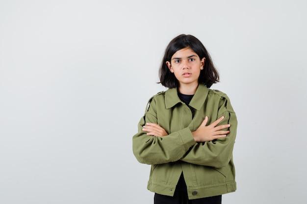 Teen girl standing avec bras croisés en veste verte de l'armée et à la perplexité. vue de face.