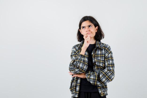 Teen girl standing in pensant pose, regardant loin en chemise décontractée et à la réflexion. vue de face.