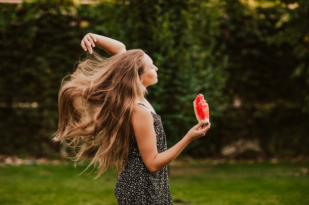 Teen girl with long hair holdingslice de pastèque dans le jardin