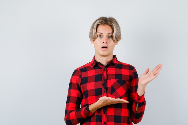 Teen mâle blond en chemise décontractée à la pensive, vue de face.