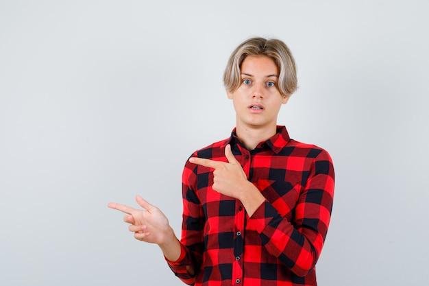 Teen mâle blond en chemise décontractée pointant vers la gauche et pensif, vue de face.