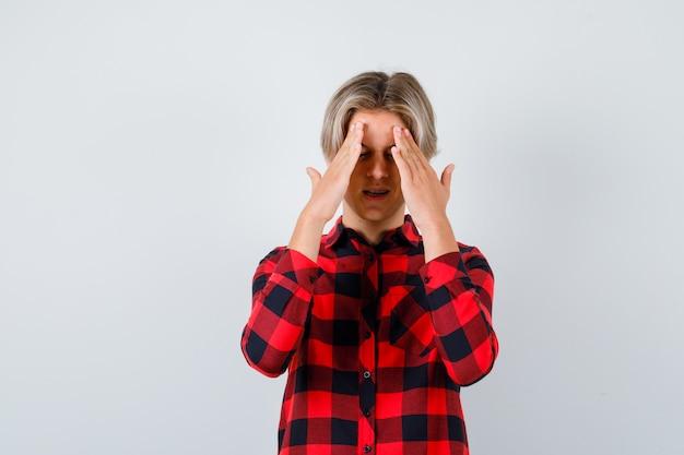 Teen mâle blond en chemise décontractée souffrant de maux de tête et semblant douloureux, vue de face.