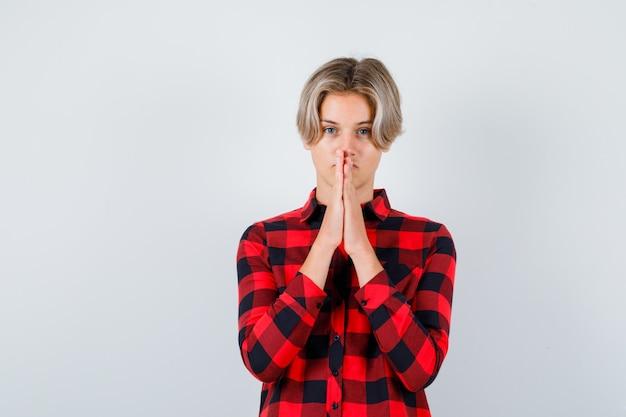 Teen mâle blond avec les mains en geste de prière en chemise décontractée et à l'espoir, vue de face.
