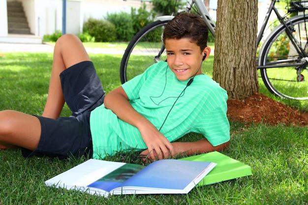 Teen souriant garçon étudiant casque de jardin livre