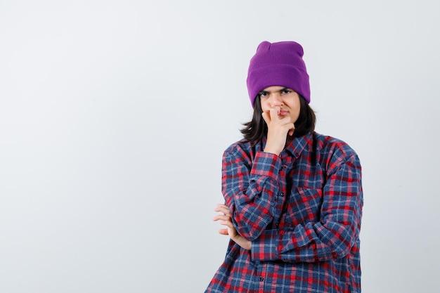 Teen woman étayer le menton à la main beanie pensif