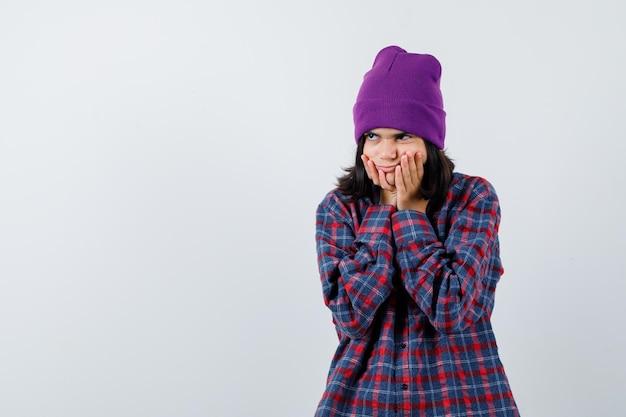 Teen woman étayer le menton sur les mains en chemise à carreaux et bonnet à pensive