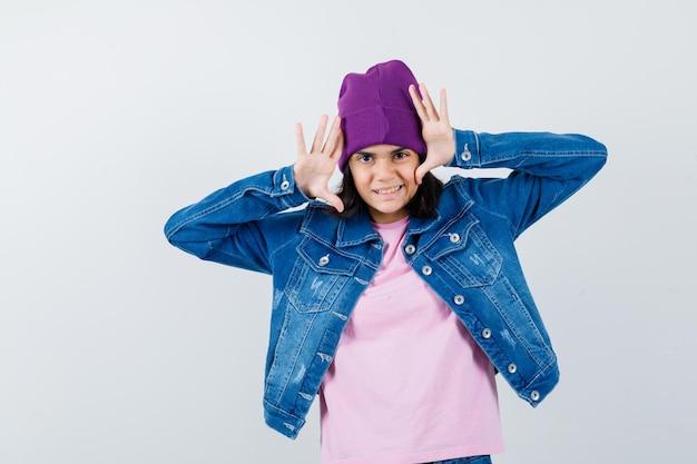Teen woman gardant les mains levées près de la tête en bonnet veste t-shirt à drôle