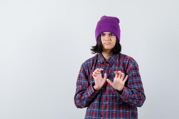 Teen woman gardant les mains pour se défendre en chemise à carreaux et bonnet
