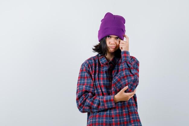 Teen woman holding finger on head en chemise à carreaux et bonnet à pensive