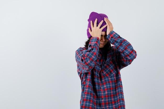 Teen woman holding hands on head en chemise à carreaux et bonnet à la tristesse