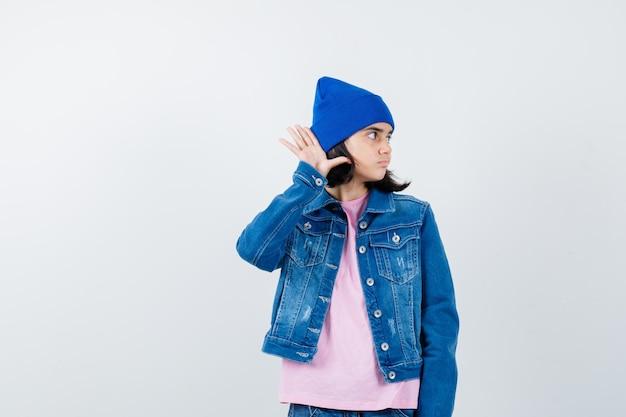 Teen woman in pink t-shirt veste en jean beanie tenant la main près de l'oreille
