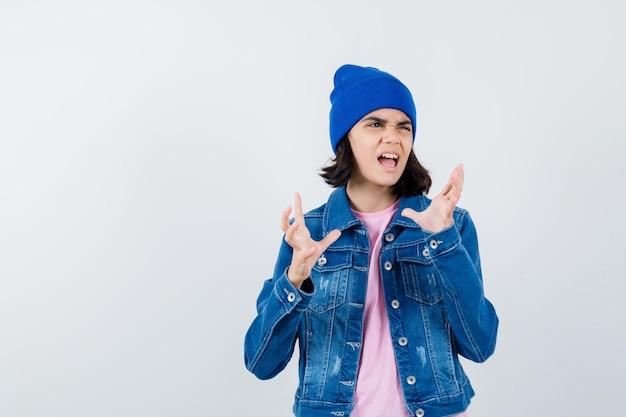 Teen woman in pink t-shirt veste en jean et bonnet levant les mains de manière surprise