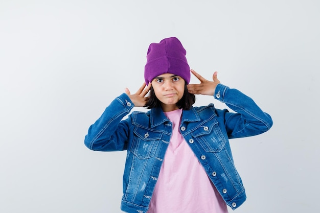 Teen woman in t-shirt jacket beanie gardant les mains derrière les oreilles à curieux