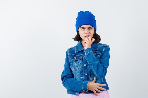 Teen woman leaning chin on hand grimaçant en t-shirt rose à l'anxiété