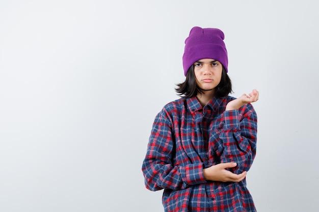 Teen woman levant la main de manière perplexe beanie à la confusion