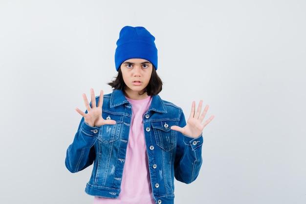 Teen woman levant les mains en abandon posent à la peur
