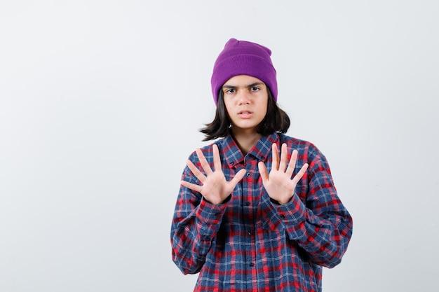 Teen woman levant les paumes pour s'arrêter en chemise à carreaux bonnet violet à la peur