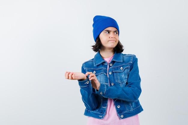 Teen woman se gratter le bras en regardant le côté droit en t-shirt rose à heureux