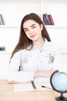 Teenage étudiant assis à table dans la salle de classe