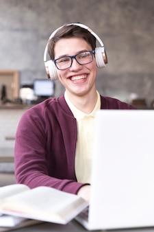 Teenage étudiant dans des lunettes et des écouteurs assis à table dans la salle de classe