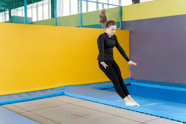 Teenage woman jumping on trampoline in fitness centre