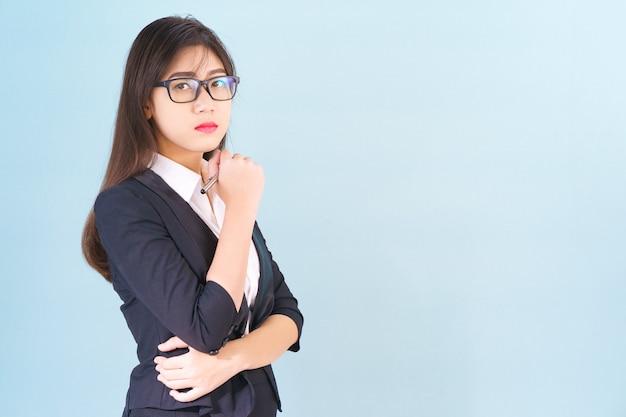 Teenage young asian wearing suit avec main de soutien sur le menton isolé