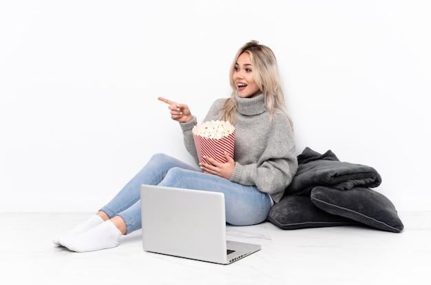 Teenager blonde woman eating popcorn tout en regardant un film sur l'ordinateur portable en pointant le doigt sur le côté et en présentant un produit