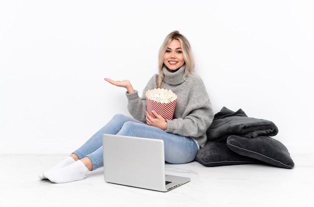Teenager blonde woman eating popcorn tout en regardant un film sur l'ordinateur portable tenant copyspace imaginaire sur la paume pour insérer une annonce