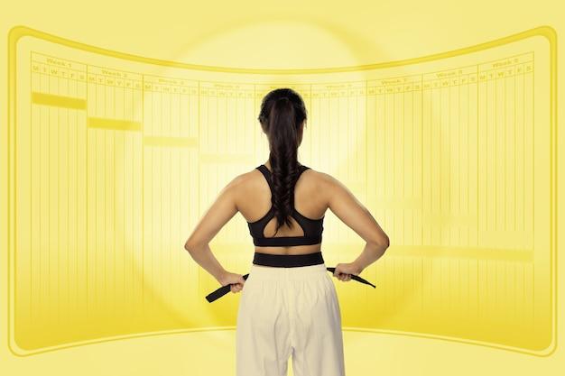 Teenager kid a la ceinture noire de judo, karaté, taekwondo. l'athlète regarde le calendrier de planification du projet pour s'entraîner, s'entraîner et faire de l'exercice. vue latérale arrière arrière de girl in zen style fond jaune