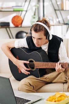 Teenge boy dans les écouteurs suivant les accords sur l'écran du portable lors de l'apprentissage d'une nouvelle chanson