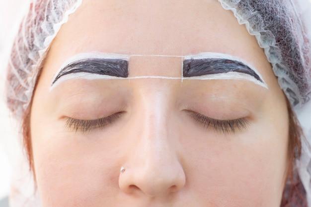 Teinture des sourcils. salon de beauté. la jeune fille se couche les yeux fermés sur la procédure de teinture des sourcils. le maître des sourcils applique une brosse sur les sourcils du client.