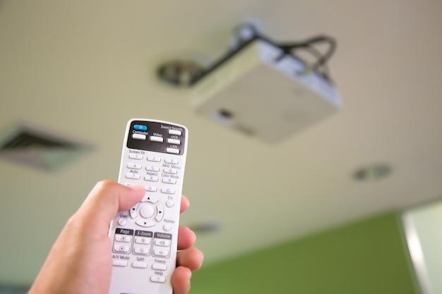 La télécommande allume le plafond du projecteur numérique dans la salle de conférence.