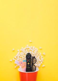 Télécommande. billets de cinéma et lunettes de soleil dans le seau de pop-corn