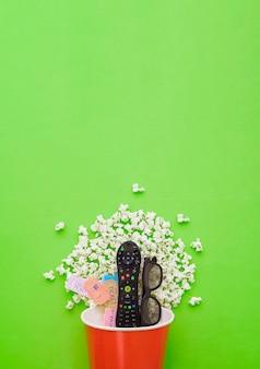 Télécommande et billets de films dans le seau à pop-corn