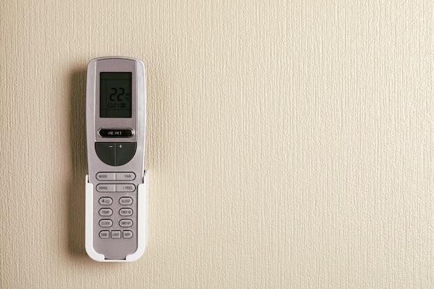 Télécommande de climatiseur sur mur en béton blanc.