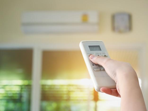 Télécommande à main dirigée vers le climatiseur