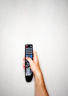 Télécommande noire du téléviseur dans une main masculine sur un fond gris clair, vue de dessus