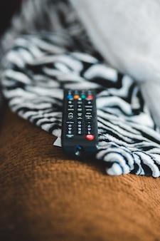 Télécommande noire sur textile marron