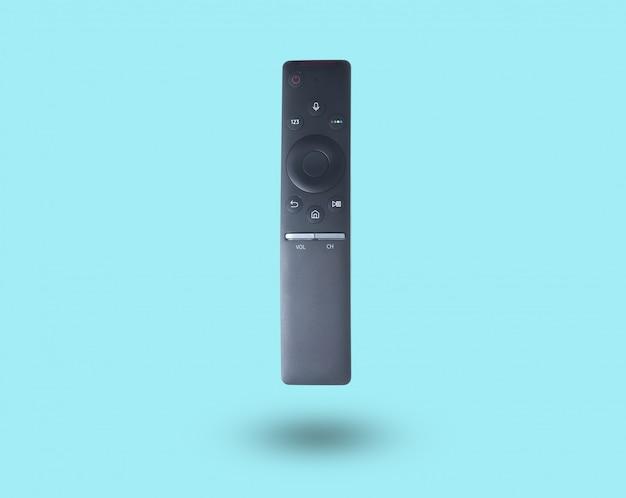 Télécommande smart tv noire isolée sur table bleue