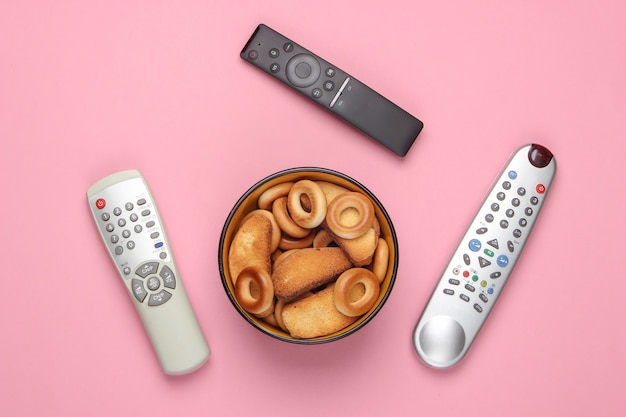 Télécommande tv et bol de crackers sur un rose pastel.