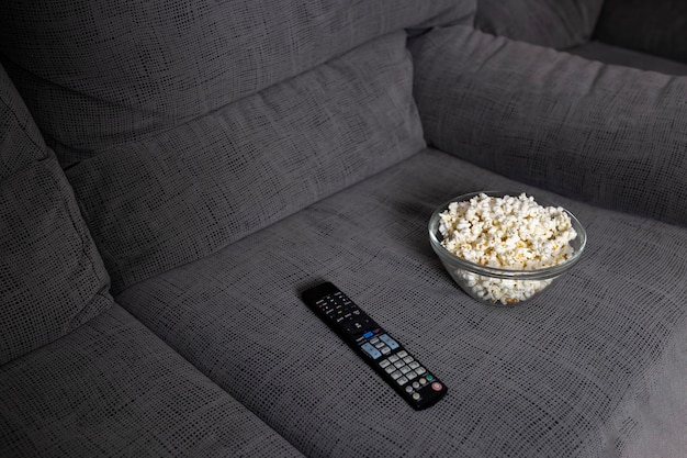 Télécommande tv et pop-corn dans un fauteuil gris
