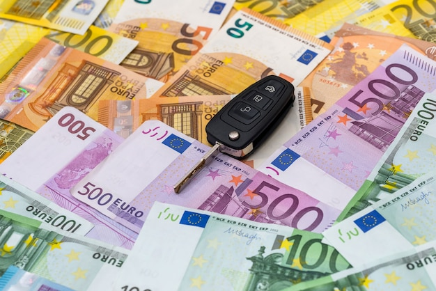 Télécommande de voiture sur fond de billets en euros