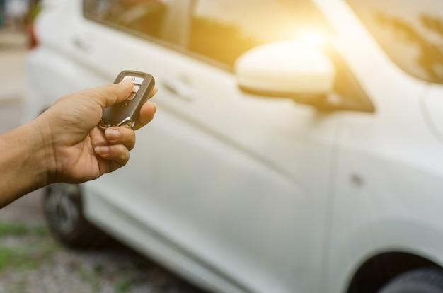 Télécommande de voiture par clé intelligente, main tenant la clé intelligente pour verrouiller les portes de la voiture blanche
