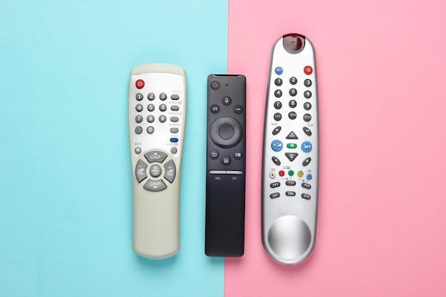 Télécommandes tv sur un pastel bleu-rose.
