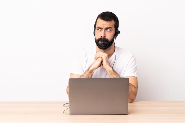 Telemarketer homme caucasien travaillant avec un casque et avec un ordinateur portable ayant des doutes tout en regardant.