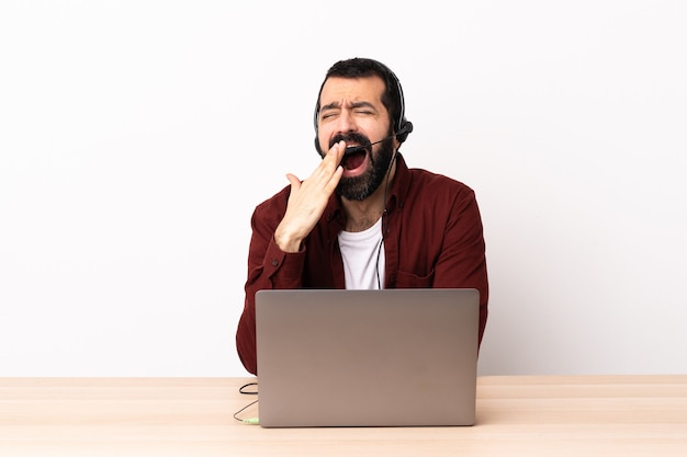 Telemarketer homme caucasien travaillant avec un casque et avec un ordinateur portable bâillant et couvrant la bouche grande ouverte avec la main.