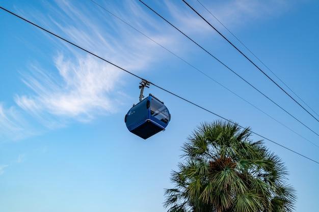 Téléphérique contre un ciel bleu clair et de grands palmiers