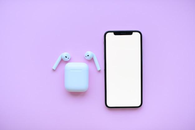 Téléphone et air pods sur fond rose