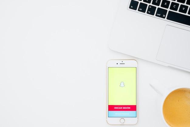 Téléphone avec application snapchat, café et ordinateur portable