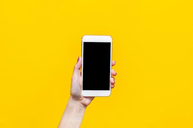 Téléphone blanc avec écran noir dans une main féminine isolée sur un mur jaune de couleur vive